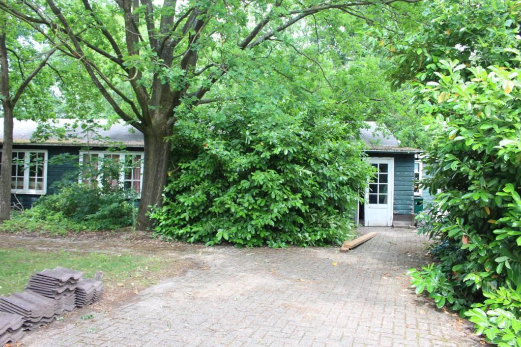 Oude barak uit het woonoord Baarschot van groen hout met witte kozijnen nu nog aanwezig.