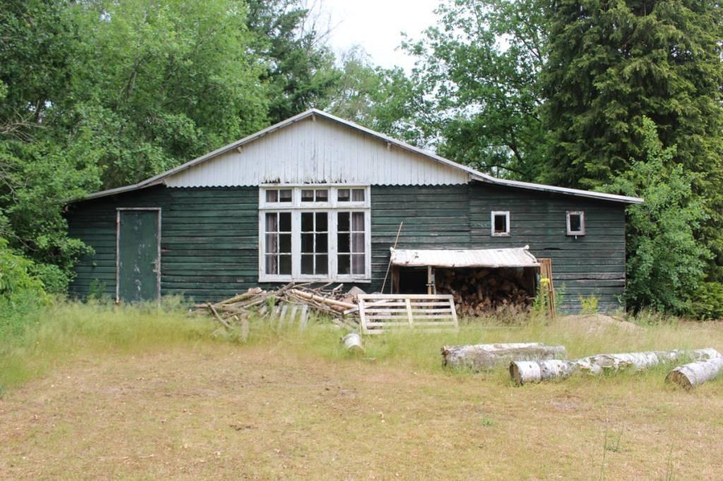 De achterkant van de barak in woonoord Baarschot. Boven de kozijnen zijn de gaten in het hout duidelijk te zien, maar ook op ander plekken kun je tussen de planken gaten zien.