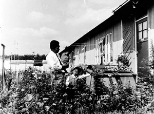 Man met kinderen in een tuin in woonoord Snodenhoek te Elst.